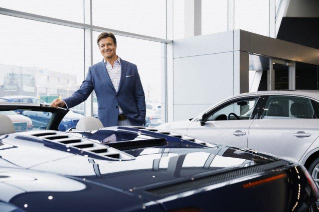 Man looking at convertible in car dealership showroom